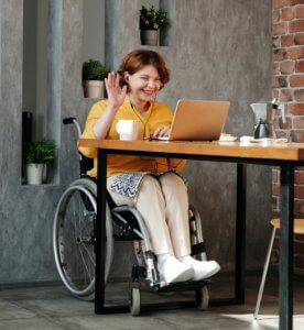 Woman in black wheelchair at laptop PA Pool